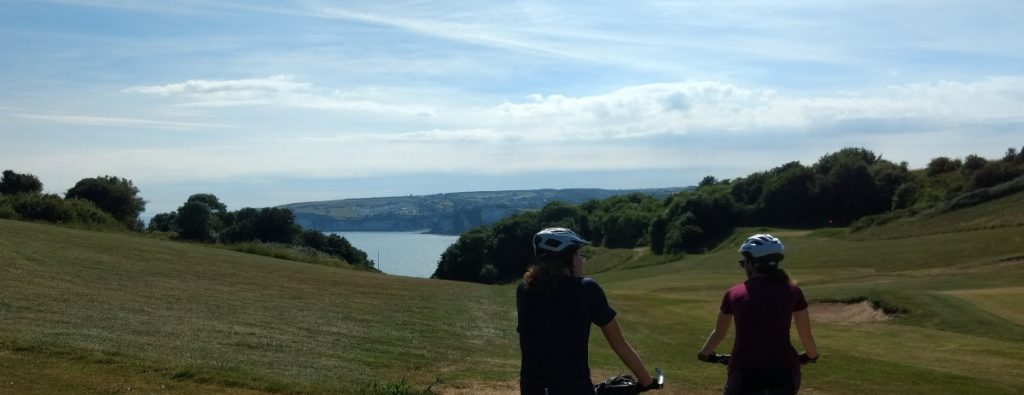 Cyclists riding down slope towards a bay