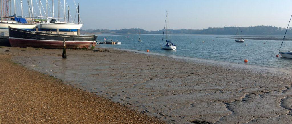 Shingle tidal beach with boats on River Deben